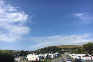 Sunny July day at Lobb Fields, Caravans and tents in a large green field