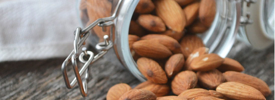 Almonds spilling out of a glass jar